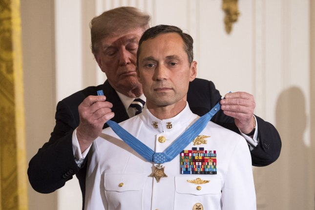 President Donald Trump awards the Medal of Honor to retired U.S. Navy Seal Master Chief Britt Slabinski for heroic action during a battle in Takur Ghar, Afghanistan, during a ceremony at the White House on Thursday in Washington, D.C. Photo by Kevin Dietch/UPI