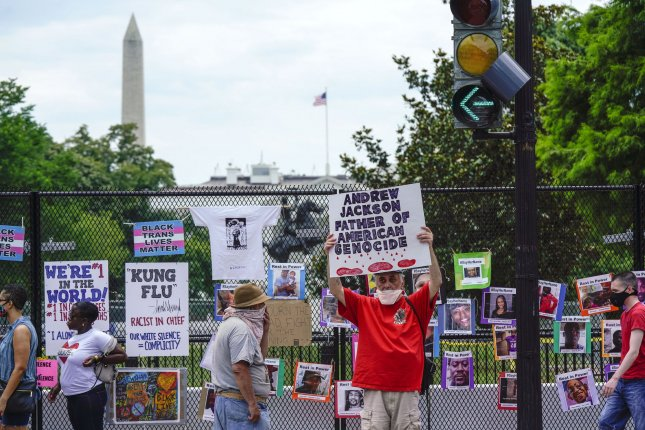 A man holds a sign in Black Lives Matter Plaza while standing in front of the General Andrew Jackson Statue in Lafayette Square late last month. File Photo by Leigh Vogel/UPI