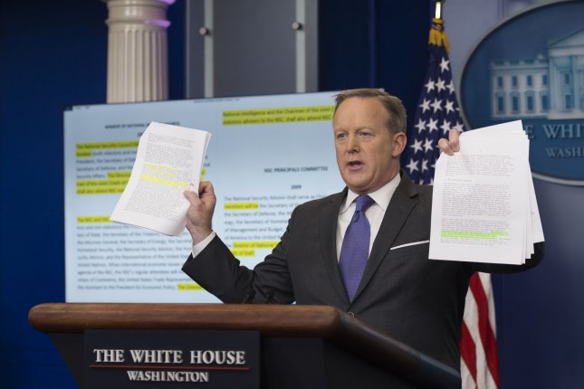 White House spokesman Sean Spicer holds up documents containing the language regarding the structure of President Donald Trump's National Security Council during a press briefing at the White House on Monday. Spicer said the CIA director has been added to the NSC. Photo by Molly Riley/UPI