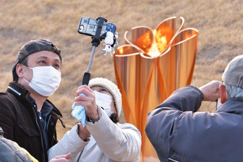 People take photos of the Olympic Flame at Ishinomaki Minamihama Tsunami Recovery Memorial Park in Ishinomaki, Miyagi-prefecture, Japan on Friday. Photo by Keizo Mori/UPI