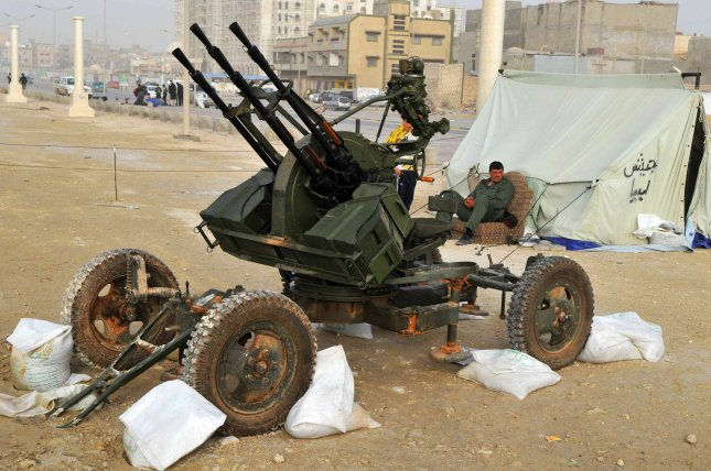 Libyans sit next to anti-aircraft guns in Benghazi, Libya on March 2, 2011. Gadhafi warned the West against intervening in the rebellion against his rule. UPI/Mohamaad Hosam