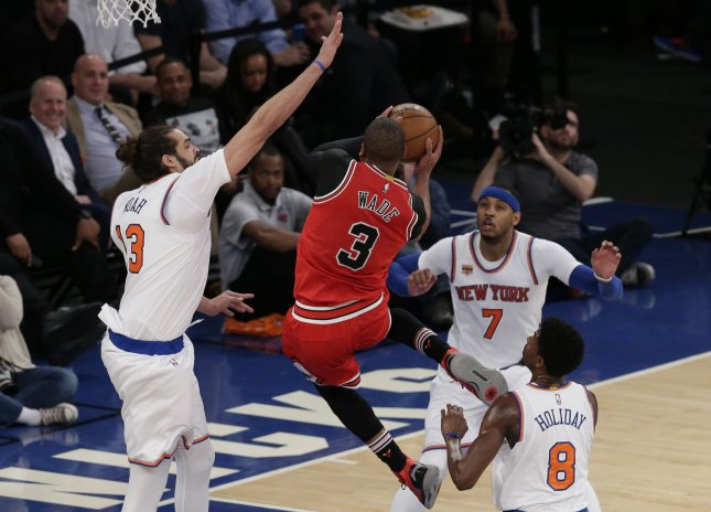 New York Knicks Joakim Noah and Carmelo Anthony watch and Chicago Bulls Dwyane Wade drive to the basket in the second half at Madison Square Garden in New York City on January 12, 2017. The Knicks defeated the Bulls 104-89. Photo by John Angelillo/UPI