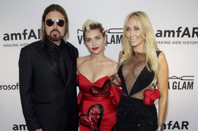 Miley Cyrus (C) with dad Billy Ray Cyrus (L) and mom Tish Cyrus at the amfAR Inspiration gala on June 16, 2015. The singer announced Monday that Billy Ray will mentor her team on The Voice. File Photo by John Angelillo/UPI