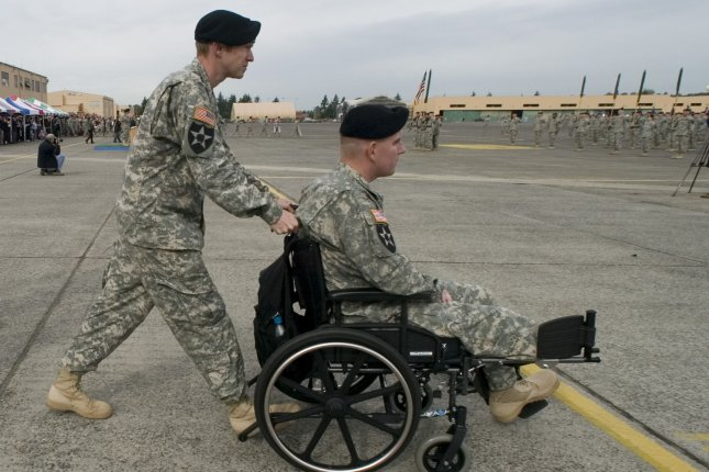 Capt. Dave Rogers pushes Capt. A.J. Tong as he joins his unit with other wounded soldiers during welcome home ceremonies for the 3rd Brigade, 2nd Infantry Division at Fort Lewis in Tacoma, Wash., on October 11, 2007. Tong had his right foot blown off by an improvised explosives device. Soldiers from the 3rd Stryker Brigade were deployed in Iraq from June 2006 to September 2007. File Photo by Jim Bryant/UPI