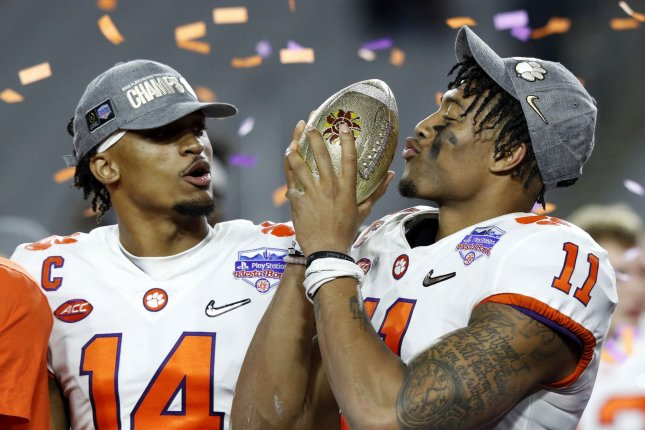 Clemson Tigers players Diondre Johnson (14) and Isiah Simmons (11) celebrate with the Fiesta Bowl trophy after defeating the Ohio State Buckeyes in the College Football Playoff semifinal game Saturday at the Fiesta Bowl in Glendale, Ariz. Photo by Aaron Josefczyk/UPI