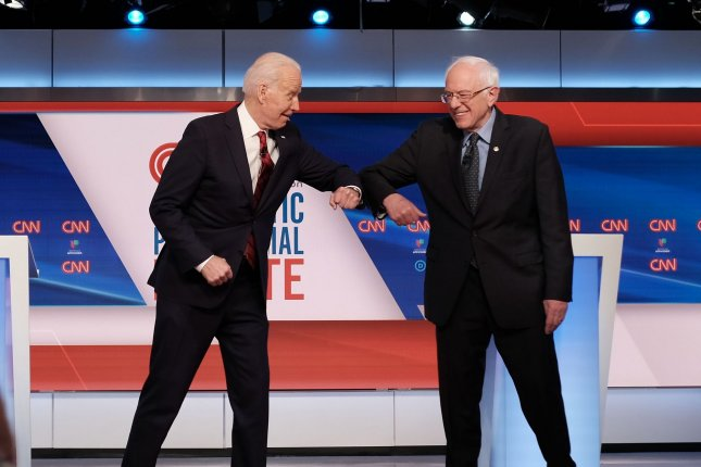 Democratic candidates Joe Biden and Bernie Sanders bump elbows before participating in a debate at a CNN studio in Washington, D.C. Because of the coronavirus, the debate was held without an audience and in accordance with CDC guidelines, their podiums six feet apart. Photo courtesy of CNN