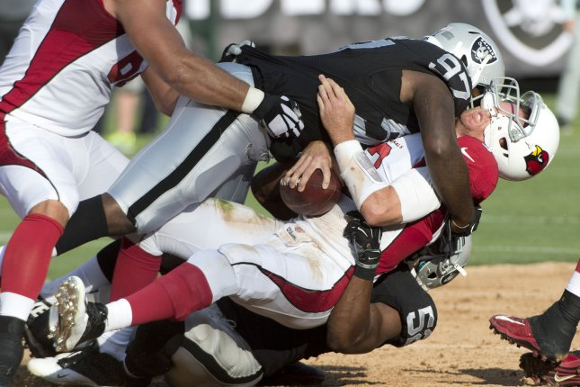 Arizona Cardinals QB Carson Palmer (3) is sacked for a seven yard loss by Oakland Raiders Mario Edwards Jr. (97) in the second quarter at O.co Coliseum in Oakland, California on August 30, 2015. The Cardinals defeated the Raiders 30-23. Photo by Terry Schmitt/UPI