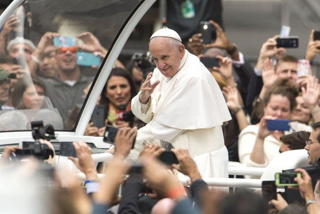 Pope Francis waves to the crowd as he arrives for Mass on the Benjamin Franklin Parkway concluding his three-city U.S. visit in Philadelphia on Sept. 27, 2015. File Photo by Kevin Dietsch/UPI