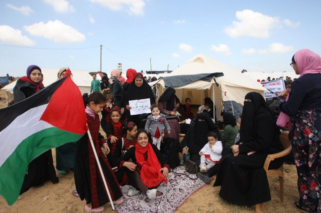 A family sits by tents pitched by Palestinians on the Gaza border with Israel during a Great March of Return protest in Rafah, Southern Gaza on March 30, 2018. Organizers called for a mass demonstration Saturday to mark the anniversary of protests demanding return to land in Israel. File Photo by Ismael Mohamad/UPI.