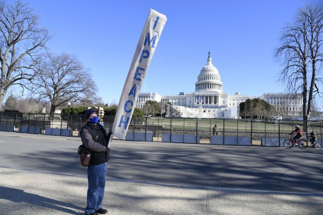 A demonstrator holds a banner on Sunday calling for the impeachment of President Donald Trump, in front of the U.S. Capitol in Washington, D.C. Photo by Mike Theiler/UPI