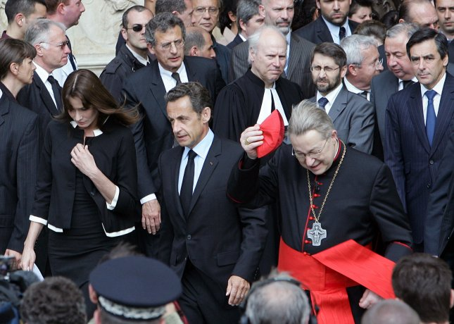 French President Nicolas Sarkozy and his wife, Carla Bruni-Sarkozy, walk with Archbishop Andre Vingt-Trois (R) as they leave the Notre Dame Cathedral in Paris, June 3, 2009 after attending a religious ceremony in memory of the victims of the missing Air France flight A330-200. The plane carried 228 people when it disappeared on June 1, between Rio de Janeiro and Paris. At top L is Air France-KLM President Jean-Cyril Spinetta. (UPI Photo/Eco Clement)