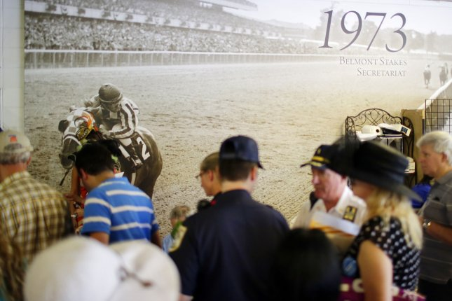 Fans gather around a poster of 1973 Triple Crown winner Secretariat on June 7, 2014. On June 9, 1973, Secretariat, having won the Kentucky Derby and Preakness, captured racing's Triple Crown with a spectacular victory in the Belmont Stakes. File Photo by John Angelillo/UPI
