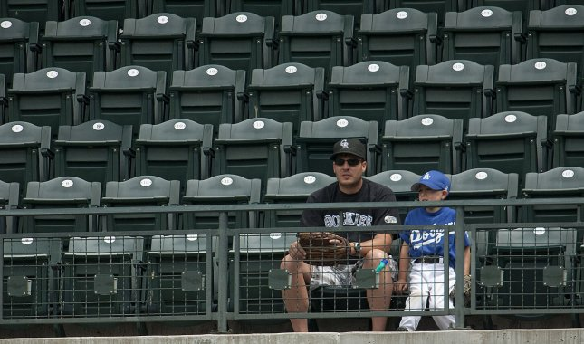 Early to the stadium, this father-son duo enjoy a Father's Day at the ballpark before the start of the Detroit Tigers-Colorado Rockies' inter-league game at Coors Field in Denver on June 15, 2011. UPI/Gary C. Caskey