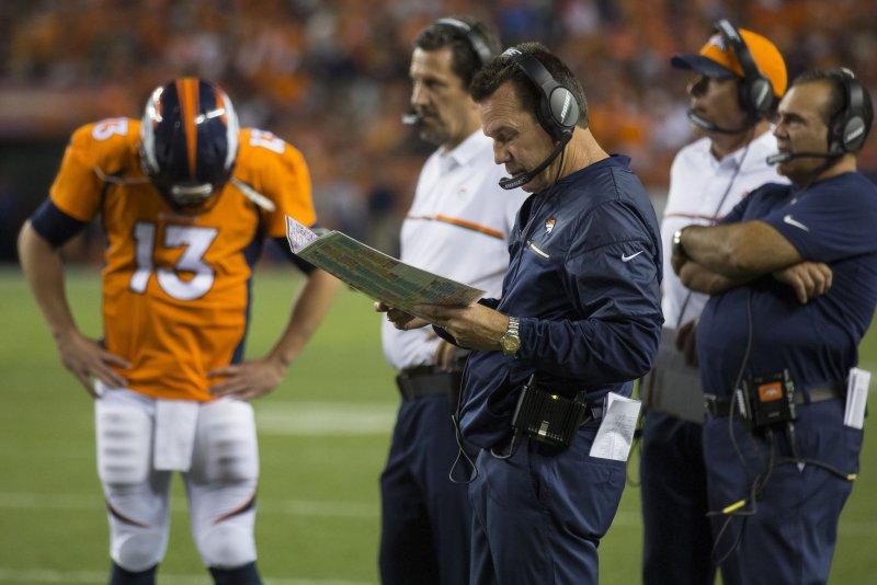 Denver Broncos head coach Gary Kubiak (C) talks with quarterback Trevor Siemian in the NFL's 2016 season opener. Photo by Gary C. Caskey/UPI