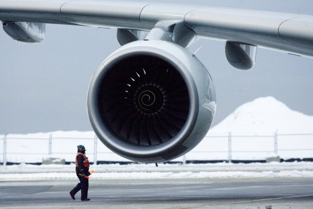 A worker walks beneath one of four largeRolls Royce Trent 900 engines on an Airbus A380 at Vancouver International Airport in Vancouver, British Columbia, Canada. File Photo by Heinz Ruckemann/UPI