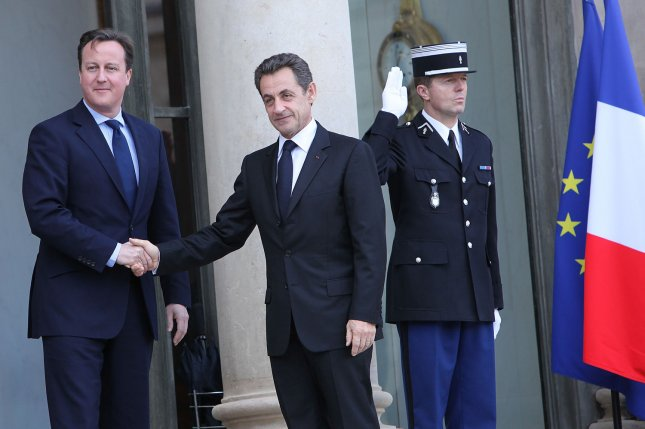 British Prime Minister David Cameron (L) shakes hands with former French President Nicolas Sarkozy next to the flags of France and the European Union at a meeting in Paris in 2011. Thursday, Cameron said in a televised interview that Great Britain leaving the EU would cause self harm and wouldn't do much to stem the rising flow of migrants into Europe. File Photo by David Silpa/UPI