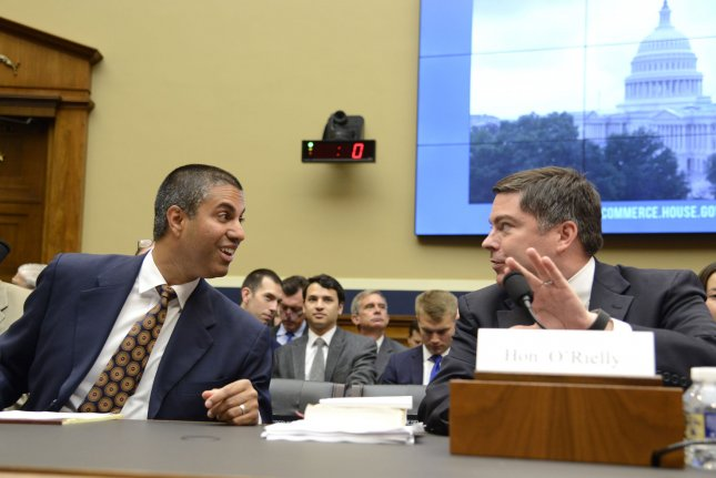 FCC Chairman Ajit Pai, left, confers with Commissioner Michael O'Rielly at a House Communications and Technology Subcommittee hearing on July 25. File Photo by Mike Theiler/UPI