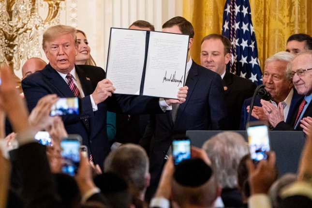 President Donald J. Trump holds up an executive order combating anti-Semitism he signed at a Hanukkah event on Wednesday. Photo by Ken Cedeno/UPI