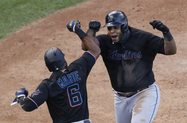 Miami Marlins designated hitter Jesus Aguilar (24) celebrates with Starling Marte (6) after hitting a two-run home run against the Chicago Cubs in the seventh inning of their NL Wild Card Series game Wednesday at Wrigley Field in Chicago. Photo by Kamil Krzaczynski/UPI