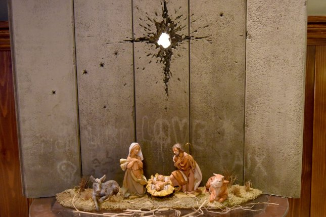 Banksy's Scar of Bethlehem shows a Nativity scene in front of the Israeli separation wall, on display Monday at the artist's Walled-Off Hotel in Bethlehem, West Bank. Photo by Debbie Hill/UPI