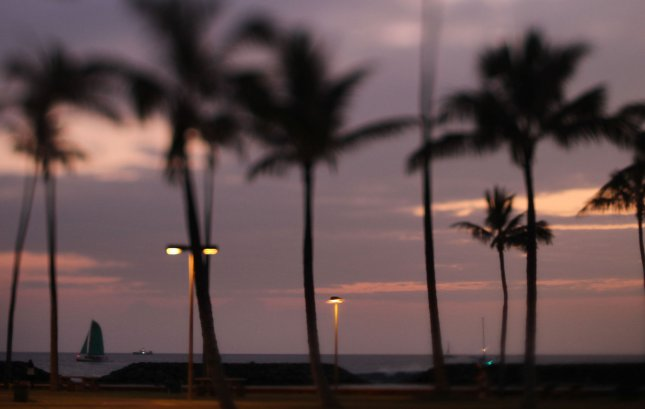 A lone sailboat sails offshore Magic Island next to Ala Moana Beach Park fronting the orange glow during sunset in Honolulu, Hawaii on January 4, 2012. UPI/Cory Lum