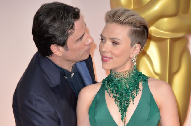John Travolta steals a kiss from Scarlett Johansson as they arrive on the red carpet at the 87th Academy Awards at the Hollywood & Highland Center in Los Angeles on February 22, 2015. Photo by Kevin Dietsch/UPI