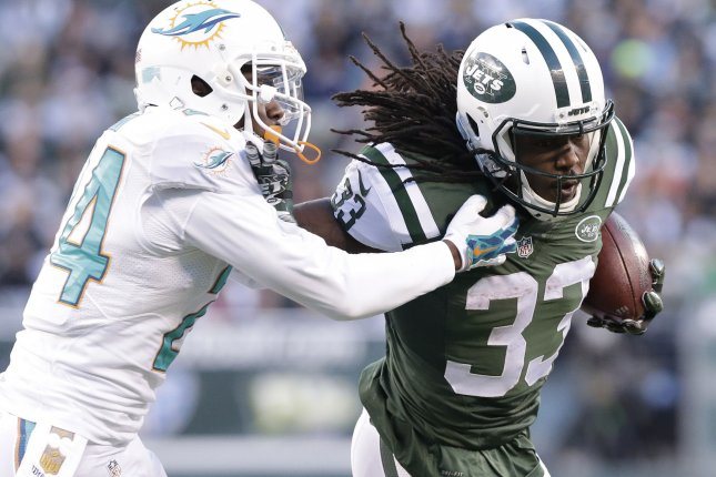 Miami Dolphins' Brice McCain grabs the jersey of former New York Jets Chris Ivory in the second half at MetLife Stadium in East Rutherford, New Jersey on November 29, 2015. The Jets defeated the Dolphins 38-20. Photo by John Angelillo/UPI