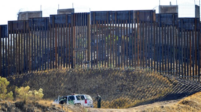 A Boarder Patrol officer stands near his truck as he checks the fence along the boarder between the United States and Mexico in Nogalas, Arizona, December 15, 2011. UPI /Art Foxall