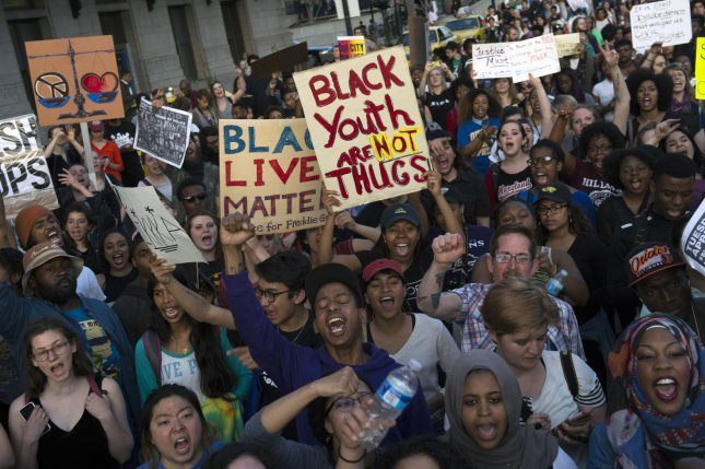 Demonstrators march to protest the death of Freddie Gray on April 29 in Baltimore. Freddie Gray died after suffering a spinal injury while being arrested by Baltimore City Police earlier this month. The first trial of police officers allegedly involved in his death begins Monday. File photo by Kevin Dietsch/UPI