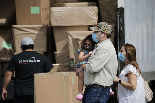 A family wearing protective face masks walk by a moving company worker and truck in in New York City on May 27, 2020. On Friday, an appeals court said a CDC eviction moratorium could remain in place. File Photo by John Angelillo/UPI