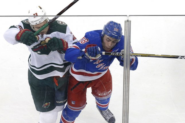 New York Rangers' John Gilmour and Minnesota Wild's Nino Niederreiter collide in the first period on February 23 at Madison Square Garden in New York City. Photo by John Angelillo/UPI