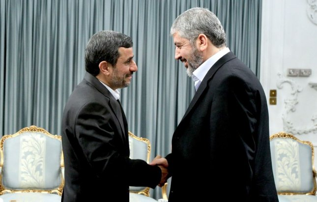 Iranian President Mahmoud Ahmadinejad (L) shakes hands with Hamas leader Khaled Mashaal during an official meeting in presidential palace in Tehran, Iran on Monday Oct 3,2011. UPI/Iranian Presidential Office Handout