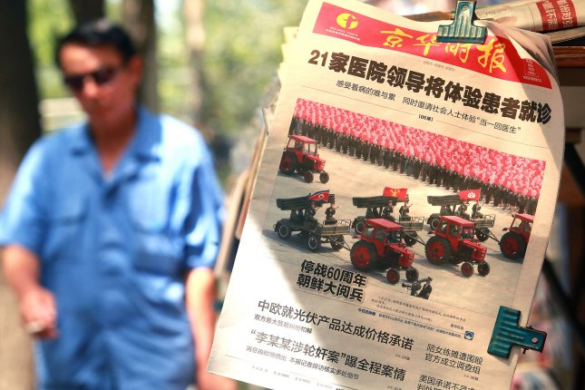 A Chinese newspaper features a front-page story on a North Korean military parade including tractors pulling missiles, through Pyongyang's main square. UPI/Stephen Shaver