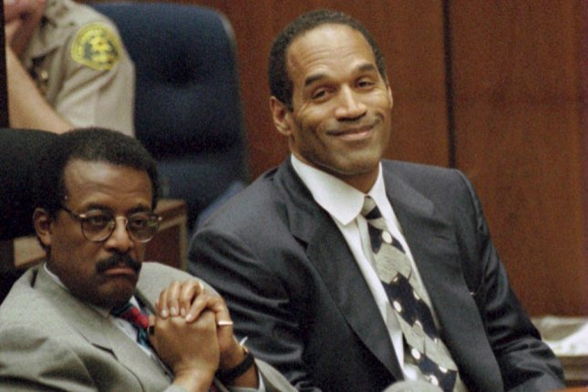 Lead defense attorney Johnnie Cochran (L) and defendant O.J. Simpson listen to testimony March 21, 1995, by Brian Kato Kaelin. On October, 3, 1995, Simpson was acquitted of charges that he killed his former wife, Nicole Brown Simpson, and her friend, Ron Goldman. Pool Photo by Myung J. Chun/UPI