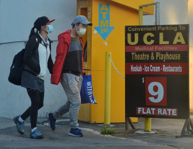A couple wearing protective masks walk to their car near the UCLA campus in Los Angeles in March, as the coronavirus pandemic was starting to ramp up in the United States. Photo by Jim Ruymen/UPI