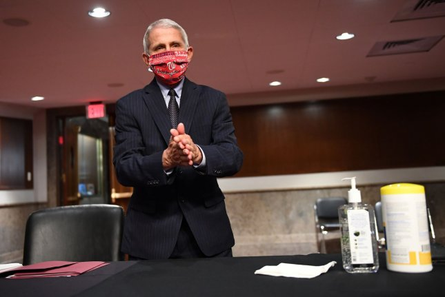 Dr. Anthony Fauci, director of the National Institute for Allergy and Infectious Diseases, cleans his hands as he prepares to testify on Tuesday before a Senate committee. Photo by Kevin Dietsch/UPI