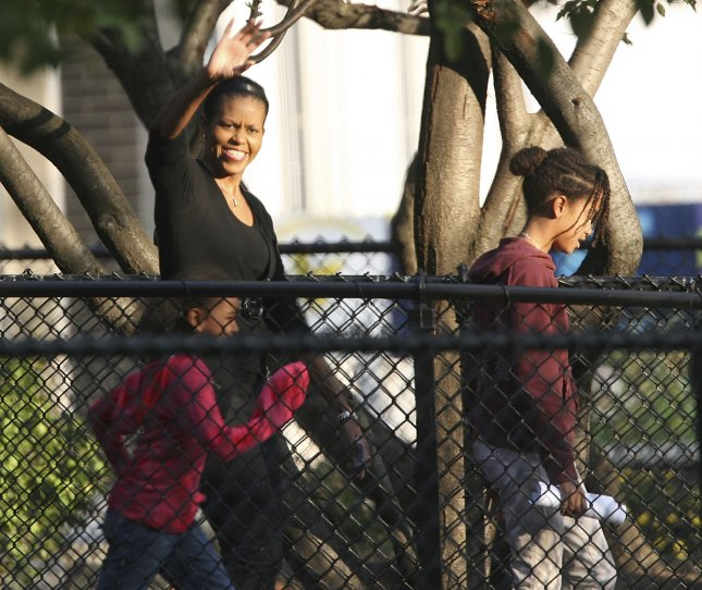 Michelle Obama waves as she leaves her polling place with daughters Sasha (L) and Malia (R) on November 4, 2008 in Chicago. (UPI Photo/Brian Kersey)