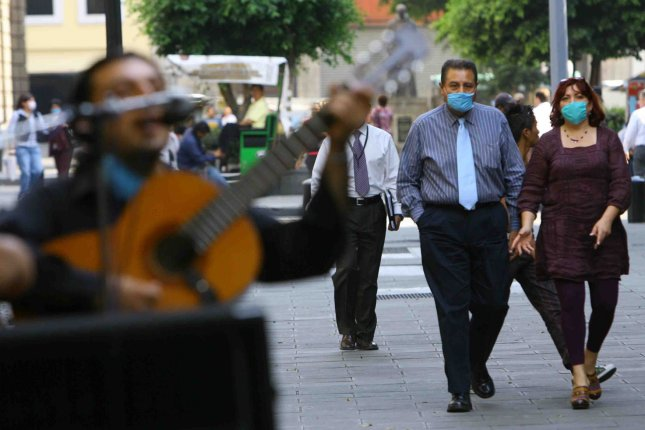 Commuters wear protective masks they make their way along a downtown street in Mexico City on April 27, 2009. The death toll from the swine flu epidemic in Mexico doubled on Monday and the World Health Organization raised the alert level. (UPI Photo/Israel Rosas)