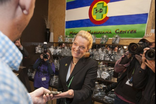 Marijuana store owner Toni Fox smiles while receiving money from official first customer Sean Azzariti of Boston for legal recreational marijuana at the 3D Cannabis Center in Denver on January 1, 2014. Colorado has already generated more than $20 million in marijuana revenue since legalization. UPI/Gary C. Caskey
