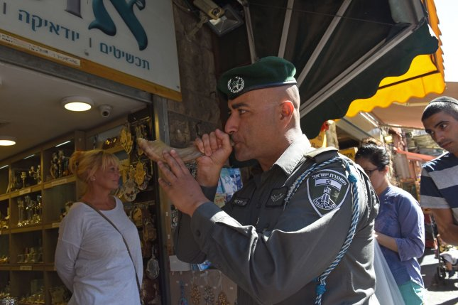 An Israeli border police blows a shofar, a ram's horn, in the Mahane Yehuda Market in Jerusalem, Israel, for Rosh Hashana, the Jewish New Year, that starts at sunset Sunday Photo by Debbie Hill/UPI