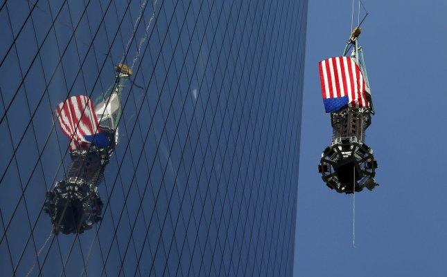 The final section of spire is raised by crane to the top of One World Trade Center skyscraper in New York City on May 2, 2013. The final section, comprising the 17th and 18th pieces, will bring the building to its iconic height of 1776. Once the pieces are installed, at a later date, the spire will make One World Trade Center the tallest building in the Western Hemisphere. UPI/John Angelillo