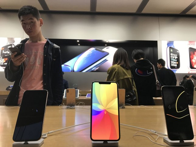Chinese shoppers check out the latest iPhones and computers at Apple's flagship store in Beijing on November 13, 2018. Apple lowered its revenue guidance for its first fiscal quarter in 2019, citing poor iPhone sales in China in a letter to investors. Photo by Stephen Shaver/UPI