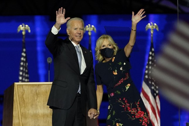 President-elect Joe Biden and his wife, Jill Biden, wave to supporters on Saturday in Wilmington, Del., after he became the projected winner. Pool Photo by Andrew Harnik/UPI