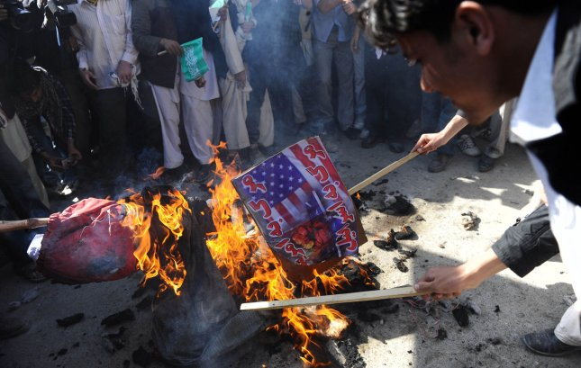 Afghan university students burn a U.S. flag during a demonstration in Kabul on October 25, 2009. Furious Afghans protested over allegations that Western troops fighting the Taliban had set fire to a copy of the Koran.(UPI Photo/Hossein Fatemi)