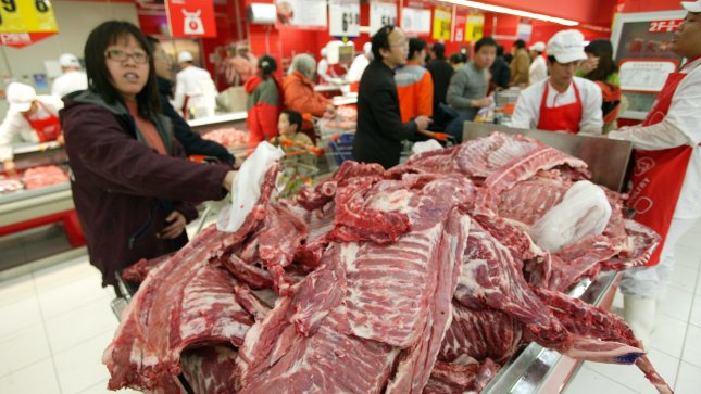 Chinese shoppers pick through sides of beef in Beijing. (UPI File Photo/Stephen Shaver)