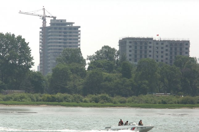 Tourists sightsee in a speed boat past new building projects in the North Korean city Sinuiju, across the Yalu River from Dandong, China's largest border city with North Korea. South of Sinuiju in Pyongyang, the number of taxis is growing. Photo by Stephen Shaver/UPI