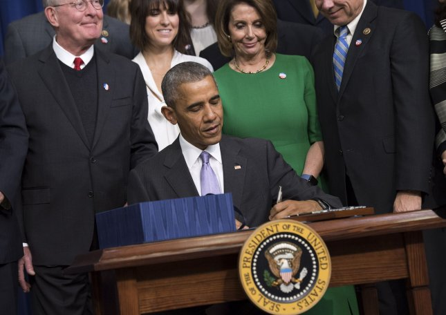 President Barack Obama signs the 21st Century Cures Act as he is joined by lawmakers and supporters during a ceremony in the Eisenhower Executive Office Building in Washington, D.C. on Tuesday. This bill will make new investments to address the heroin and prescription opioid epidemic, accelerate discoveries in cancer research as part of the Cancer Moonshot, expand the Administration's BRAIN and Precision Medicine Initiatives, and take important steps to improve mental health and the Food and Drug Administration's drug development process. Photo by Kevin Dietsch/UPI