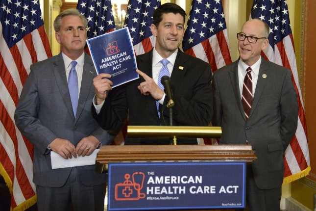 House Speaker Paul Ryan holds a copy of the new health care bill introduced by Republicans, as Majority Leader Kevin McCarthy of California, left, and Oregon Rep. Greg Walden look on on March 7. That legislation -- the American Health Care Act -- is viewed negatively by 54 percent of Americans, a new poll shows. Photo by Mike Theiler/UPI