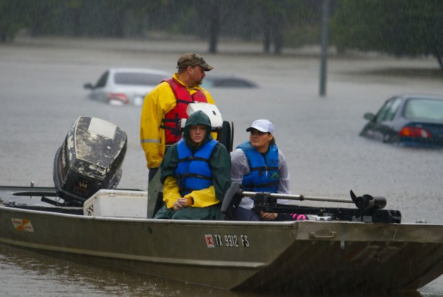 Rescue workers wait to assist families through rising flood waters in the Cypress Station neighborhood as waters rise during Tropical Storm Harvey Monday in Houston, Texas. Photo by Jerome Hicks/UPI
