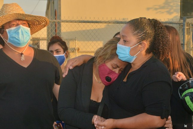Elisa Guardado is consoled by family members at a makeshift memorial near the spot where her son, Andres, 18, was fatally shot by a Los Angeles County Sheriff's deputy Thursday evening. Photo by Jim Ruymen/UPI
